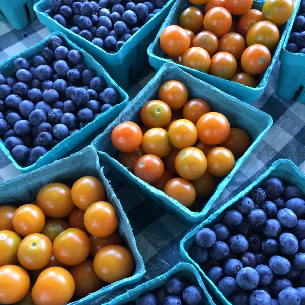 Several shades of blue; white checks on the tablecloth; orange and yellow tomatoes with a touch of green; and the outline of turquoise baskets makes this picture come alive for me.